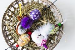 Huevos de Pascua sobre cesta de mimbre con el heno Imagen de archivo