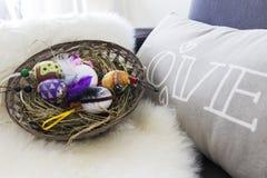 Huevos de Pascua sobre cesta de mimbre con el heno Foto de archivo libre de regalías