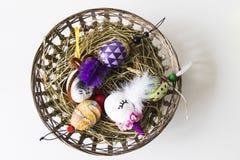 Huevos de Pascua sobre cesta de mimbre con el heno Imagenes de archivo