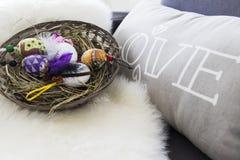 Huevos de Pascua sobre cesta de mimbre con el heno Fotografía de archivo libre de regalías