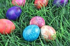 Huevos de Pascua teñidos lazo en hierba Fotos de archivo