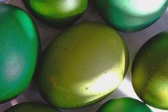 Huevos de Pascua verdes en un disco blanco Un rayo del sol que brilla en el huevo Macro de alta resolución del primer fotos de archivo libres de regalías