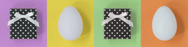 Huevos de Pascua y cajas de regalo en una bandera multicolora con los cuadrados imagenes de archivo