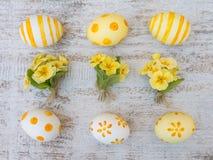 Huevos de Pascua y composición amarilla de tres ramos de la primavera Fotos de archivo