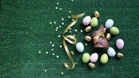 Huevos de Pascua y conejito de oro del chocolate en un fondo verde foto de archivo