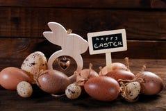Huevos de Pascua y decoraciones de madera con saludos en la pizarra Fotos de archivo