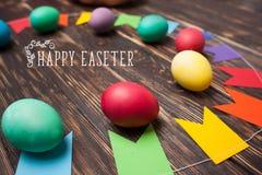 Huevos de Pascua y decoraciones del día de fiesta en un fondo de madera colorido Imágenes de archivo libres de regalías