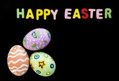 Huevos de Pascua y deletreo de la palabra en fondo negro Foto de archivo