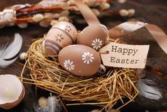 Huevos de Pascua y etiqueta de papel con saludos en jerarquía Fotografía de archivo