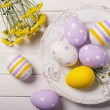 Huevos de Pascua y flores coloridos del campo en la placa Imagen de archivo libre de regalías