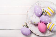 Huevos de Pascua y flores coloridos del campo en la placa Imagenes de archivo