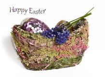 Huevos de Pascua y flovrers en una cesta Imágenes de archivo libres de regalías