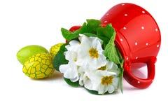 Huevos de Pascua y jarro rojo con las flores blancas Imagen de archivo