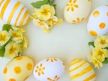 Huevos de Pascua y marco amarillo de las flores de la primavera Imagenes de archivo