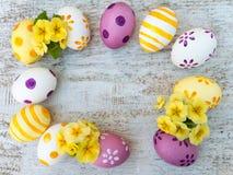 Huevos de Pascua y marco amarillo de las flores de la primavera Fotos de archivo libres de regalías