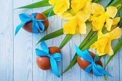 Huevos de Pascua y narcisos frescos de la primavera en fondo de madera resistido Imágenes de archivo libres de regalías