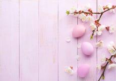 Huevos de Pascua y ramas del albaricoque floreciente en una tabla de madera rosada vieja Visión superior imágenes de archivo libres de regalías