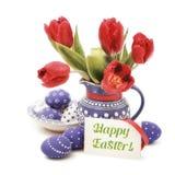 Huevos de Pascua y tulipanes rojos en florero azul en el blanco, texto Imagen de archivo