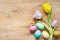 Huevos de Pascua y tulipanes simples coloridos de la primavera en fondo de madera fotos de archivo libres de regalías