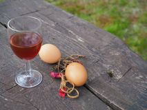 Huevos de Pascua y vidrio de vino tinto en la tabla foto de archivo libre de regalías