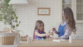 Huevos de pintura de la ni?a con su madre usando un peque?o cepillo Una familia feliz Preparaci?n de la Pascua almacen de video