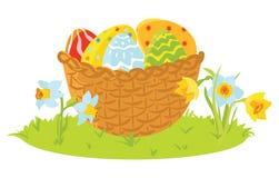 Huevos decorativos de Pascua en una cesta con las flores Imagen de archivo libre de regalías