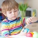 Huevos del colorante del muchacho del niño para el día de fiesta de Pascua Fotos de archivo