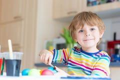 Huevos del colorante del muchacho del niño para el día de fiesta de Pascua Foto de archivo libre de regalías