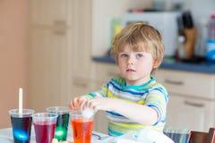 Huevos del colorante del muchacho del niño para el día de fiesta de Pascua Fotografía de archivo libre de regalías