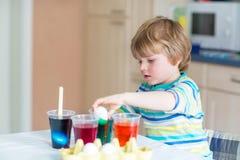 Huevos del colorante del muchacho del niño para el día de fiesta de Pascua Foto de archivo