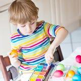 Huevos del colorante del muchacho del niño para el día de fiesta de Pascua Imagen de archivo libre de regalías