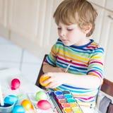 Huevos del colorante del muchacho del niño para el día de fiesta de Pascua Fotos de archivo libres de regalías
