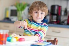 Huevos del colorante del muchacho del niño para el día de fiesta de Pascua Imagen de archivo