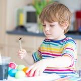 Huevos del colorante del muchacho del niño para el día de fiesta de Pascua Imagenes de archivo