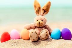 Huevos del conejito y del color de pascua en la playa arenosa cerca imagenes de archivo
