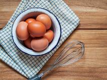 Huevos del pollo en un cuenco, servilleta del paño, batidor para batir en a cortejar imagen de archivo libre de regalías