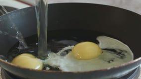3 huevos del pollo están quebrados en un sartén metrajes