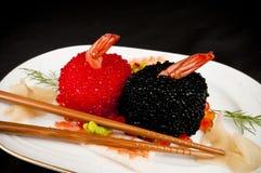 Huevos del sushi, rojos y negros de peces con los palillos. Fotos de archivo