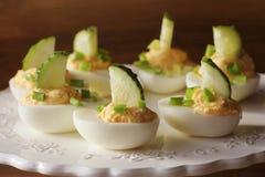 Huevos deviled picantes adornados con el pepino y el puerro en la placa blanca Fondo rústico de madera Foto de archivo libre de regalías