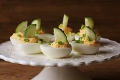 Huevos deviled picantes adornados con el pepino y el puerro en la placa blanca Fondo rústico de madera Foto de archivo