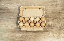 Huevos, diez huevos marrones en un paquete del cartón en una tabla de madera Fotografía de archivo