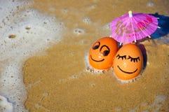 Huevos divertidos de Pascua debajo del paraguas en una playa Imagenes de archivo
