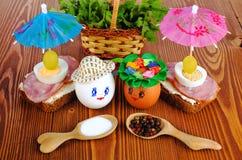 Huevos divertidos en el sombrero y la guirnalda Con los bocadillos y los paraguas Fotos de archivo libres de regalías