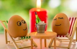 Huevos divertidos en una silla de playa que se relaja Foto de archivo