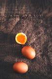 Huevos duros con la yema de huevo anaranjada en estilo rústico en cierre de madera del fondo para arriba Imagen de archivo libre de regalías