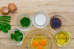 Huevos e ingredientes crudos en fondo de madera Foto de archivo