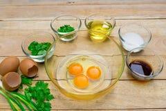 Huevos e ingredientes crudos en fondo de madera Imagen de archivo