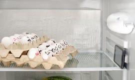 Huevos en bandejas en un estante del refrigerador, situado como en un cine Caras pintadas que miran el teléfono Imagenes de archivo