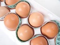 Huevos en cartón con cinta métrica Imágenes de archivo libres de regalías