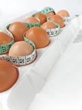 Huevos en cartón con la cinta métrica 2 Foto de archivo libre de regalías